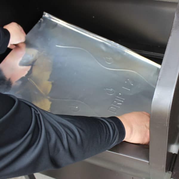 Person inserting a GMG Drip-EZ Grease Tray liner into their GMG grill