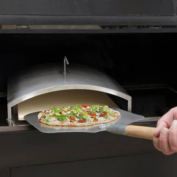 Person with a pizza peel inserting a pizza into the Wood-Fired Pizza Attachment