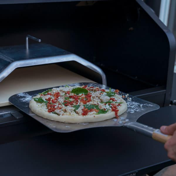 A pizza on a GMG Pizza Peel being put into a GMG Pizza Attachment